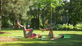 As fêmeas desportivas da aptidão que fazem a bicicleta trituram no parque vídeos de arquivo