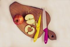 As facas e as maçãs cortadas em uma cozinha embarcam Foto de Stock