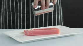 As faixas do atum são polvilhadas com as sementes de sésamo video estoque