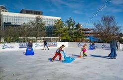 As famílias apreciam uma tarde da patinagem no gelo imagens de stock royalty free