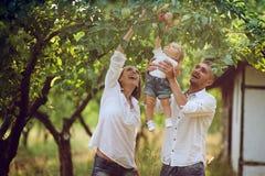As famílias com uma criança no verão jardinam foto de stock royalty free