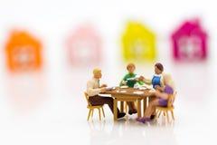 As famílias diminutas estão comemorando, comendo junto felizmente Usado no conceito do festival da família fotos de stock