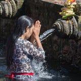As famílias do Balinese vêm ao templo sagrado da água de molas de Tirta Empul em Bali, Indonésia rezar e limpar sua alma foto de stock