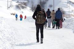 As famílias dos povos vão para uma estrada nevado fotografia de stock royalty free