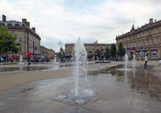 As famílias e as crianças que jogam nas fontes no ` pedestre s de St George esquadram em huddersfield yorkshire foto de stock royalty free