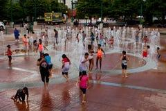As famílias obtêm o jogo molhado na fonte centenária do parque de Atlanta foto de stock