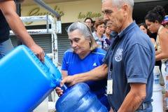 As famílias recolhidas acima das garrafas plásticas para enchê-las com os hosepipes molham em Caracas, Venezuela fotos de stock royalty free