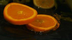 As fatias alaranjadas do fruto fresco deixam cair no vídeo de movimento lento da superfície da água vídeos de arquivo
