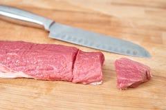 As fatias da carne crua cutted com a faca na placa de madeira fotografia de stock royalty free