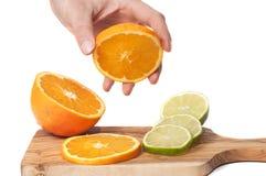 As fatias da laranja e do cal cortaram em uma placa de madeira e em uma mão que guardaram uma parte, isolada Foto de Stock Royalty Free