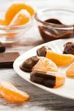 As fatias de close-up do mandarino no chocolate líquido serviram em uma placa branca Foco seletivo fotografia de stock