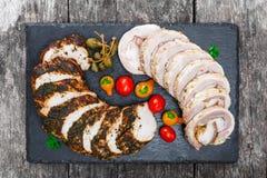 As fatias de lombinho caseiro do meatloaf, da vitela e de carne de porco enchido com os vegetais na ardósia preta apedrejam o qua Foto de Stock