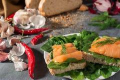 As fatias de pão frescas com salmões e aneto encontram-se em uma placa branca Metade de um pão e vegetais no fundo imagem de stock