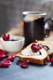 As fatias de papoila da manteiga rolam, servido com doce de cereja e o grande copo cerâmico com bebida quente Imagem de Stock Royalty Free