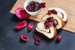 As fatias de papoila da manteiga rolam, servido com o doce de cereja que encontra-se em uma tabela preta Imagens de Stock Royalty Free