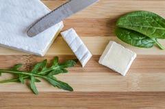 As fatias de queijo do brie na placa de corte de madeira com salada verde saem Foto de Stock Royalty Free