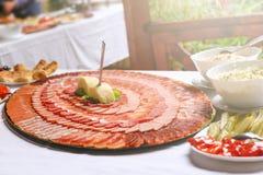 As fatias deliciosas de carne de porco secaram a carne decorada nos círculos na grande placa Grande placa com fatias da carne em  imagem de stock