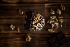 As fatias do chocolate e as nozes descascadas encontram-se em uma superfície de madeira marrom Ainda vida rústica Alimento saudáv imagens de stock royalty free