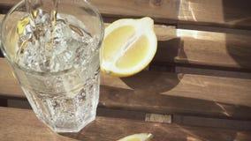 As fatias do limão na tabela e na água são derramadas em um movimento lento de vidro video estoque