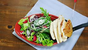 As fatias passadas ligeiramente suculentas do peito de frango são adicionadas à salada lanç verde Imagens de Stock Royalty Free
