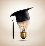 as felicitações graduam o tampão em um bulbo de lâmpada, conceito do educati Fotos de Stock