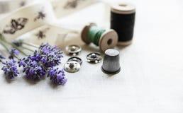 As ferramentas da costura com lavander fresco florescem no fundo de linho Carretel de madeira do vintage, trança, dedal, botões Fotografia de Stock