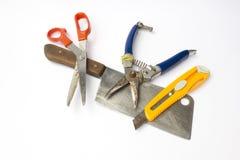 As ferramentas de corte incluem de desbastar a faca, as tesouras, as tesouras de poda e a faca da caixa isoladas no fundo branco Foto de Stock