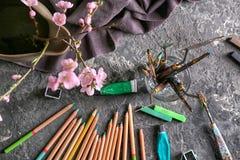 As ferramentas do artista com pinturas na tabela imagens de stock