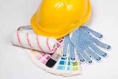 As ferramentas do pintor - escovas, luvas do trabalho, capacete amarelo e colorf Fotos de Stock Royalty Free