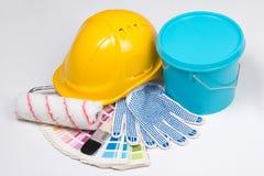 As ferramentas do pintor - escovas, luvas do trabalho, capacete e cubeta do pai Fotos de Stock
