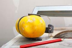 As ferramentas do trabalho viram o cortador para cortar a telha, fones de ouvido protetores imagens de stock