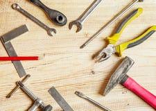 As ferramentas espalharam para fora na placa, chaves de fenda, alicates, chaves, quadrados Composição lisa dos leus, quadro Fotografia de Stock