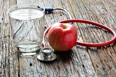 As ferramentas medicam um estetoscópio atrás de um vidro da maçã e de água para h Fotos de Stock