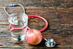 As ferramentas medicam um estetoscópio atrás de um vidro da maçã e de água para h Imagens de Stock Royalty Free