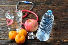 As ferramentas medicam um estetoscópio atrás de uma maçã, das laranjas e do gl da água Imagem de Stock Royalty Free