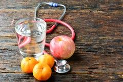 As ferramentas medicam um estetoscópio atrás de uma maçã, das laranjas e do gl da água Foto de Stock Royalty Free