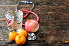 As ferramentas medicam um estetoscópio atrás de uma maçã, das laranjas e do gl da água Foto de Stock