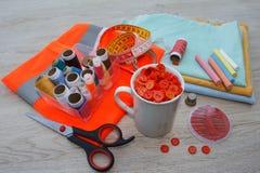 As ferramentas para costurar para o passatempo ajustaram-se na opinião superior do fundo de madeira da tabela Linha, agulhas e pa Foto de Stock