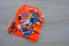 As ferramentas para costurar para o passatempo ajustaram-se na opinião superior do fundo de madeira da tabela Linha, agulhas e pa Foto de Stock Royalty Free