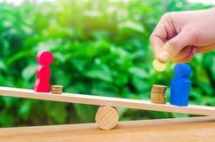 As figuras de madeira de um homem e de uma mulher estão nas escalas e nas moedas entre elas conceito da diferença de pagamento de fotos de stock royalty free