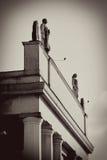 As figuras do homem e da mulher no telhado cobrem. Imagem de Stock