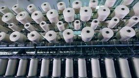 As fileiras das bobinas com fibra, enrolaram em uma planta de matéria têxtil Linha de produção industrial de matérias têxteis filme