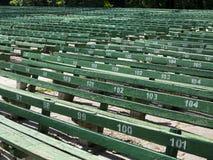 As fileiras de assentos verdes simples aproximam a cena vazia do ar livre imagem de stock royalty free