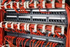 As fileiras de cabos da rede conectaram ao cubo do roteador e do interruptor foto de stock