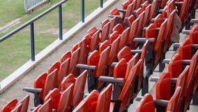 As fileiras de cadeiras de dobradura vermelhas no estádio de futebol imagem de stock
