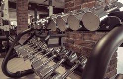 As fileiras de pesos do metal na cremalheira no vintage Brown do gym colorem a imagem tonificada Imagem de Stock Royalty Free