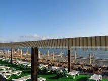 As fileiras dos sunbeds na praia, povos relaxam no beira-mar Foto de Stock Royalty Free