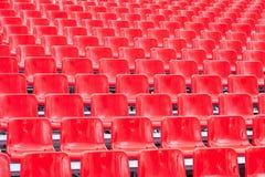 As fileiras esvaziam assentos plásticos vermelhos brilhantes Fotografia de Stock Royalty Free