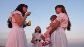 As filhas e a m?e est?o fundindo bolhas no parque no por do sol Movimento lento M?e feliz que joga com sopro das crian?as vídeos de arquivo