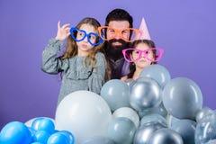 As filhas precisam o pai interessaram ativamente na vida Festa de anos Gene com as duas filhas que têm o divertimento fatherhood fotografia de stock